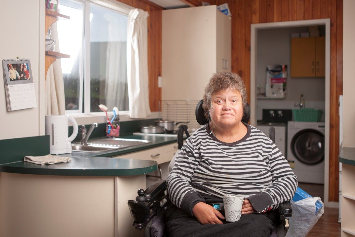 A lady in a wheel chair having a cup of tea